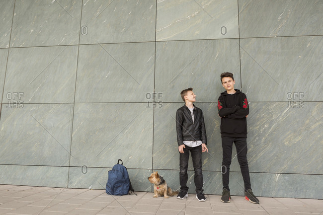 Full length of brothers standing by dog and bag against tiled gray wall in city