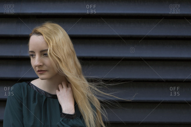 Thoughtful sad depressed young woman with long blond hair standing in front of a black ridged wall looking aside with a melancholy expression