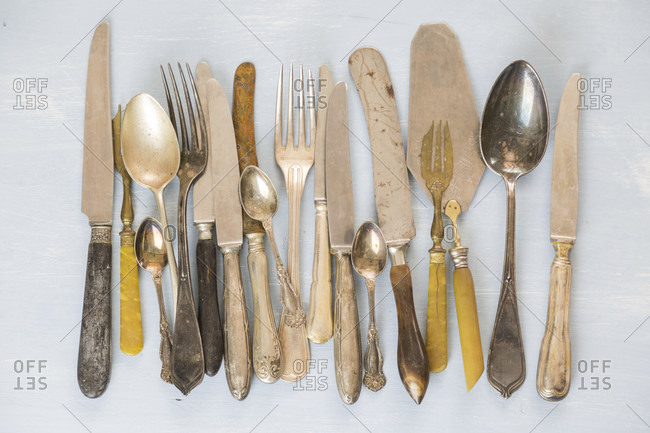 Row of assorted tarnished vintage cutlery with knives, forks and spoons, some with old bone handles viewed from above on a textured white background