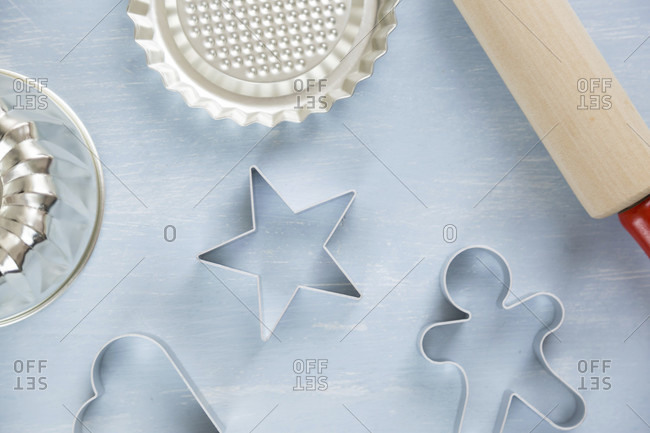 Three metal cookie cutters of different shapes with a star, heart and gingerbread man on a textured blue white background