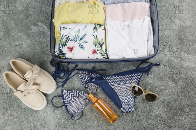 Flat lay of packed clothes luggage for summer holiday vacation