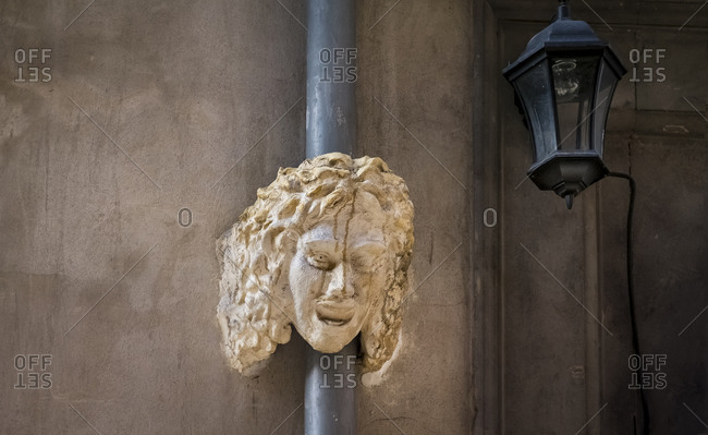 Mask and street lamp in Lyon in the Vieux Lyon district in autumn