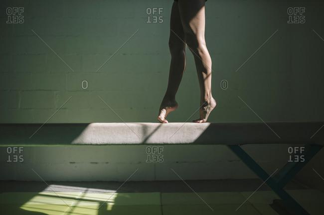 Female gymnast legs on tiptoe on top of a balance bar