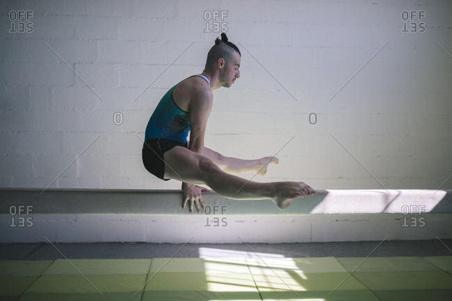 Young male gymnast doing artistic gymnastics in a gym