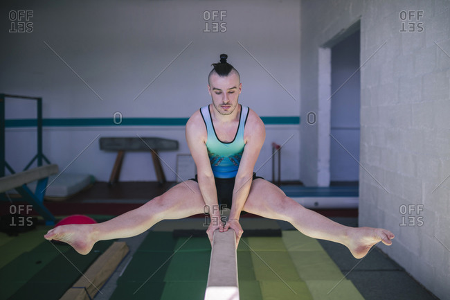 Young male gymnast doing artistic gymnastics on a balance beam in a gym