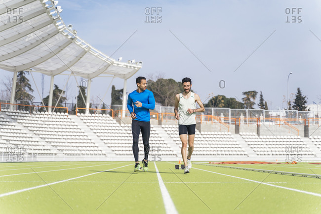 Caucasian and black male athlete practicing at a sports track