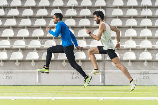 Caucasian and black male athlete running at a sports track