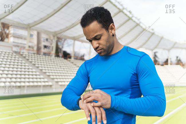 African American athlete using watch while standing on running track
