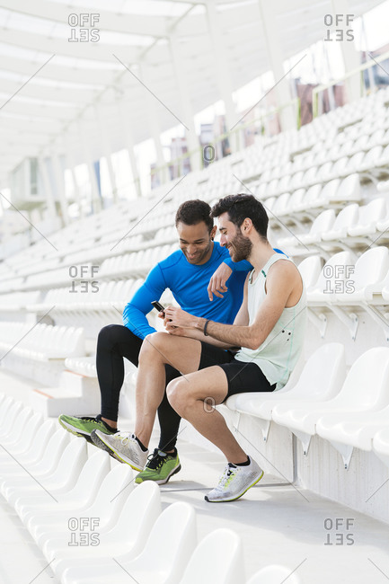 Athlete friends taking a break while using phone on white bleachers