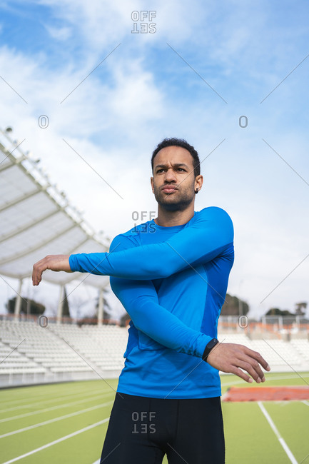 African American male athlete standing on the track stretching his arms