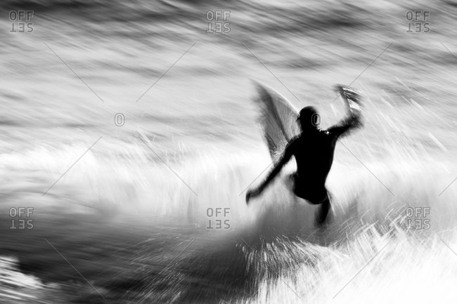 Blurred action shot of surfer riding waves in the ocean