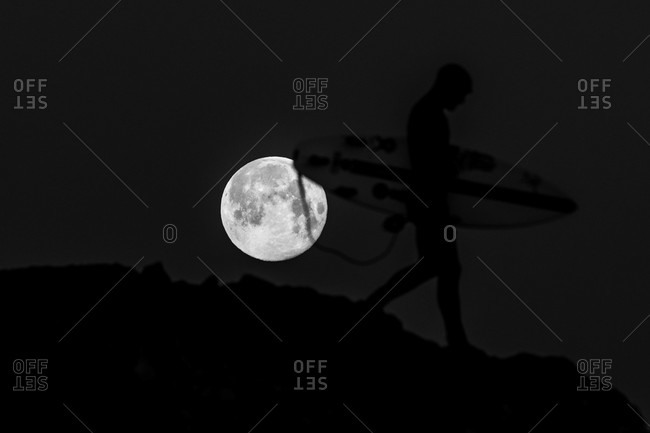 Surfer walking downhill in front of a beautiful full moon