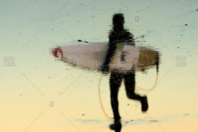 Reflection on the beach of a surfer wearing a wetsuit carrying a board