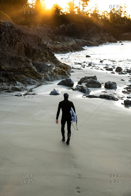 Tofino, British Columbia, Canada - April 12, 2020: Rear view of surfer in a wetsuit walking on a beach at sunset