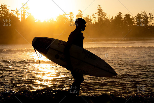 Tofino, British Columbia, Canada - April 12, 2020: Silhouette of surfer in a wetsuit walking in the waves at sunset