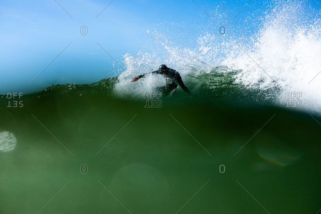 Low angle view of a surfer riding turquoise waves in the ocean