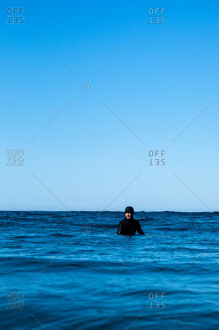 Tofino, British Columbia, Canada - April 13, 2020: Surfer waiting in the ocean for a wave under blue sky