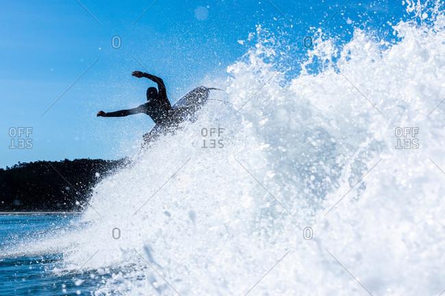 Surfer riding a fierce wave in the ocean