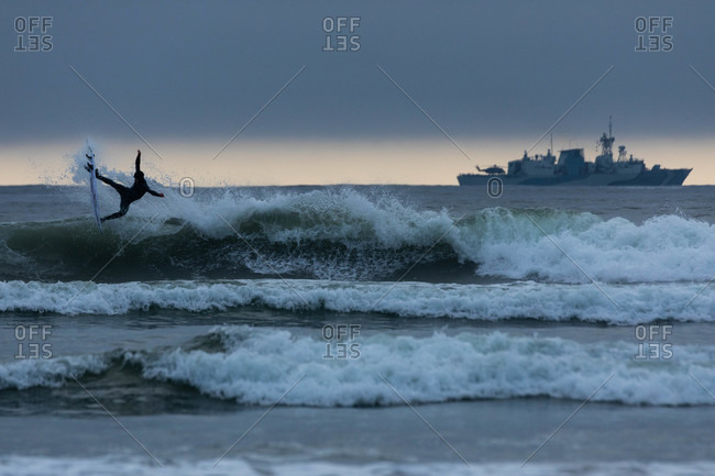 Tofino, British Columbia, Canada - April 17, 2020: Surfer riding a wave in the ocean at sunset near large ship