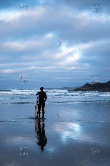 Tofino, British Columbia, Canada - April 20, 2020: Surfer in a wetsuit looking out over waves from a beach at sunset