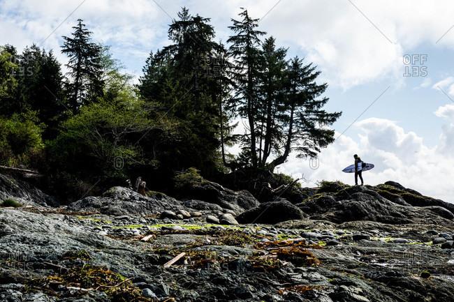 Tofino, British Columbia, Canada - April 27, 2020: Surfer walking on rocky hill with board