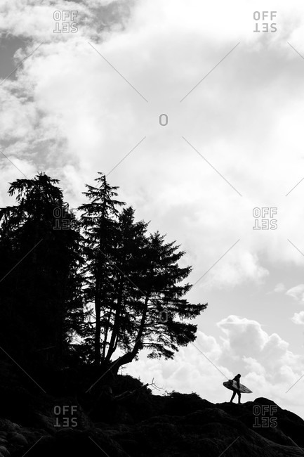 Tofino, British Columbia, Canada - April 27, 2020: Surfer walking on rocky hill with board in black and white