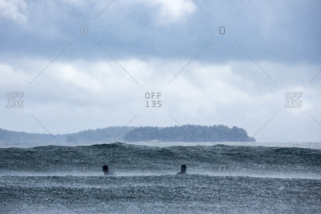 Surfers in the water as raindrops fall