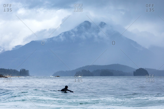 Tofino, British Columbia, Canada - April 27, 2020: Surfer in the ocean waiting on a wave near large mountain