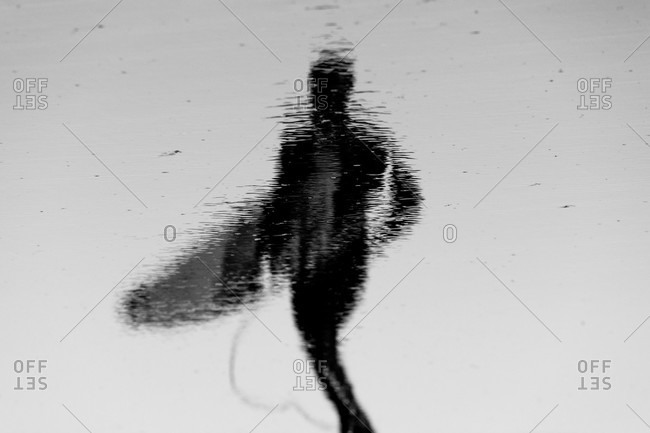 Reflection on the beach of a surfer wearing a wetsuit carrying a board in black and white