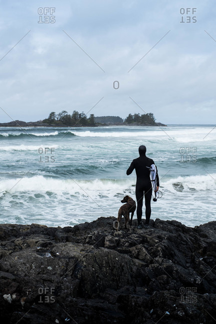 Tofino, British Columbia, Canada - May 13, 2020: Surfer holding board while looking out at the ocean with dog