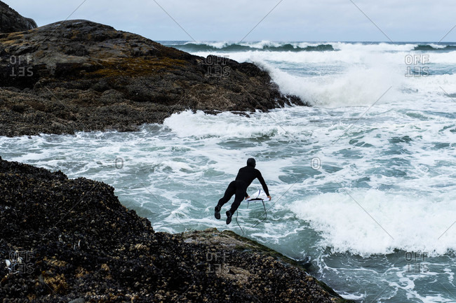 Tofino, British Columbia, Canada - May 13, 2020: Surfer jumping into the ocean waves from rocky cliff
