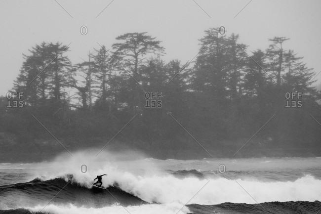 A surfer riding waves off the coast of Tofino, British Columbia, Canada in black and white