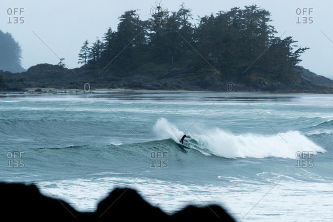 Surfer riding waves near Tofino, British Columbia, Canada