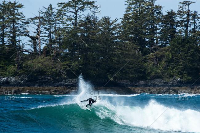 Tofino, British Columbia, Canada - May 13, 2020: A surfer riding waves off the coast of Tofino, British Columbia, Canada
