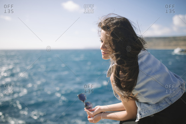 Portrait of a young woman at the beach, the wind blows her hair