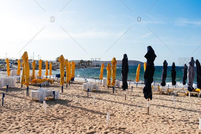 Fuengirola, Spain - June 19, 2016: Umbrellas closed on empty beach