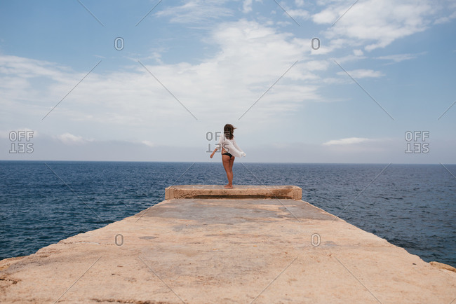 Portrait of a happy young woman standing on a pier