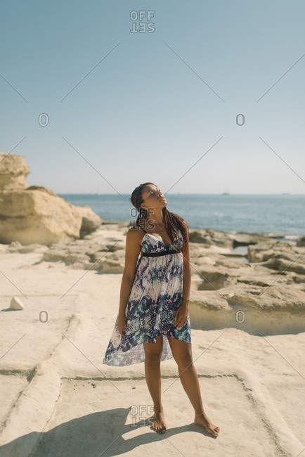 Portrait of a young African-American woman sunbathing at the beach