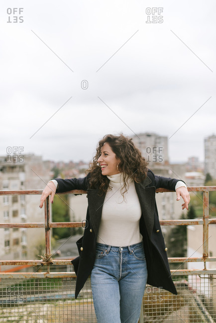Portrait of a happy young woman in her twenties at the rooftop