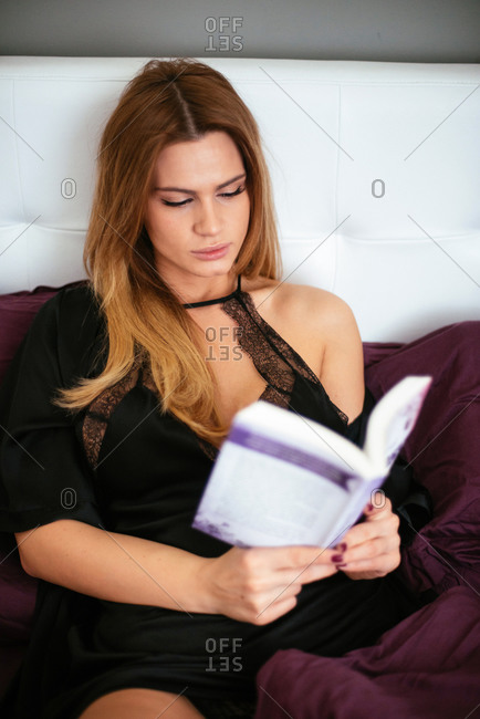 Beautiful young woman reading a book in bed