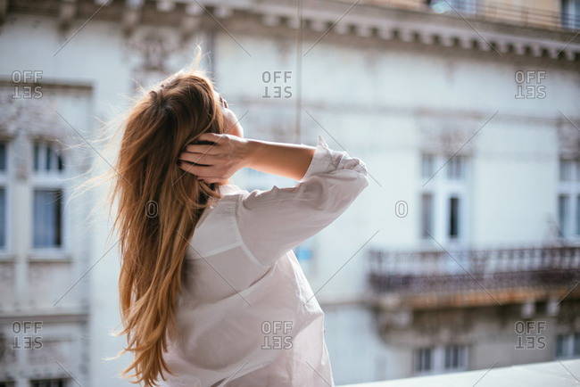 Young woman standing on balcony in a white shirt