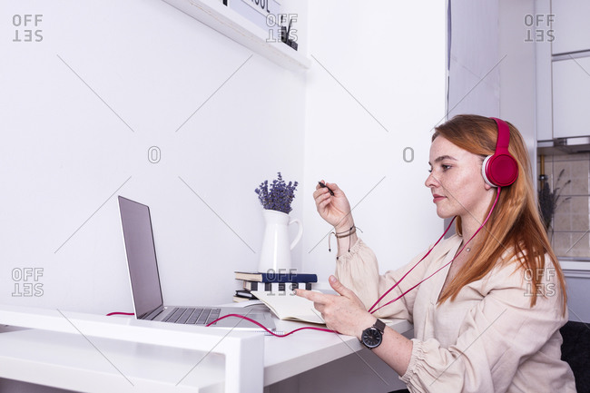 Young ginger woman online teaching from her home desk while wearing pink headphones