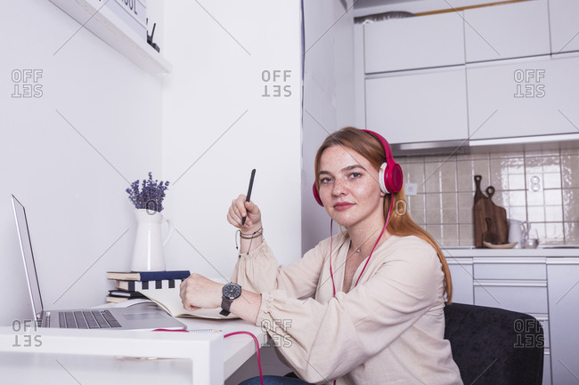 Portrait of a young ginger woman online teaching from her home desk wearing pink headphones