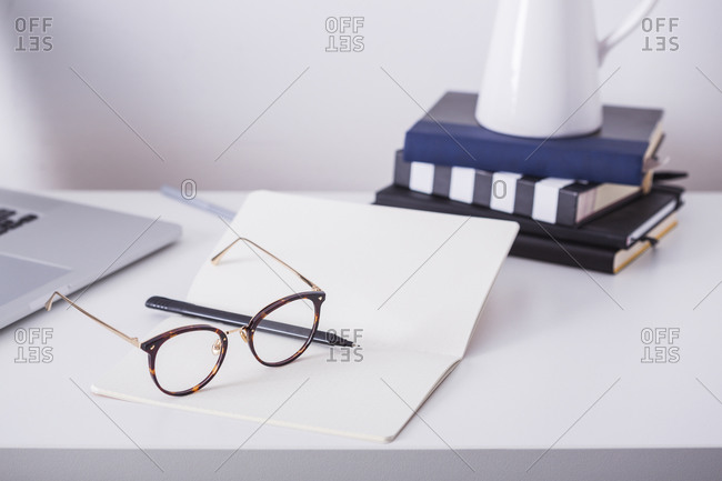 Blank open book with pen and reading glasses on desk beside laptop and stack of books