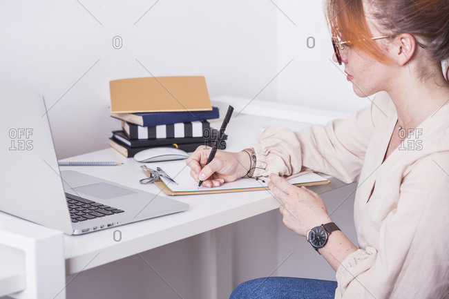 Young ginger woman writing on clipboard while teaching class from her home desk