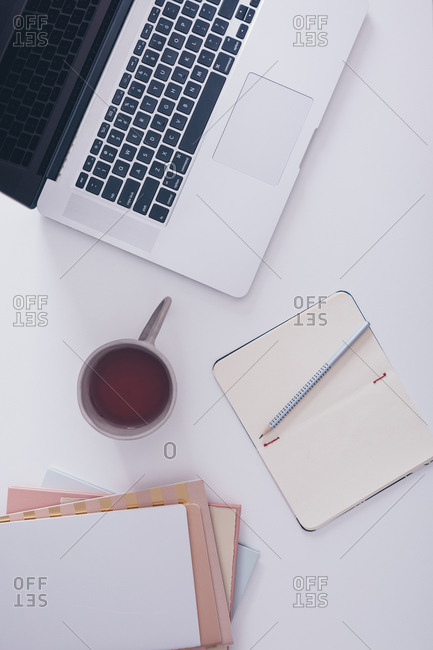 Overhead view of a blank open notebook with pencil beside laptop and tea