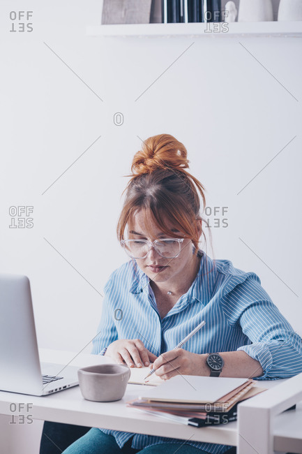 A ginger woman writing in notebook while online teaching from home