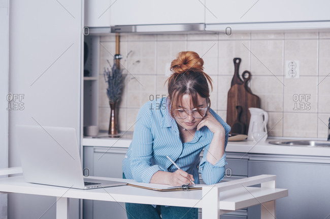 Young redhead woman writing on clipboard while teaching online from her kitchen
