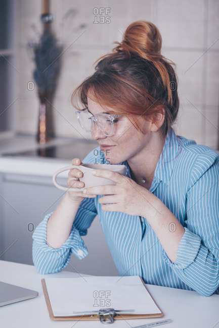 Young ginger woman drinking coffee while teaching online from her kitchen