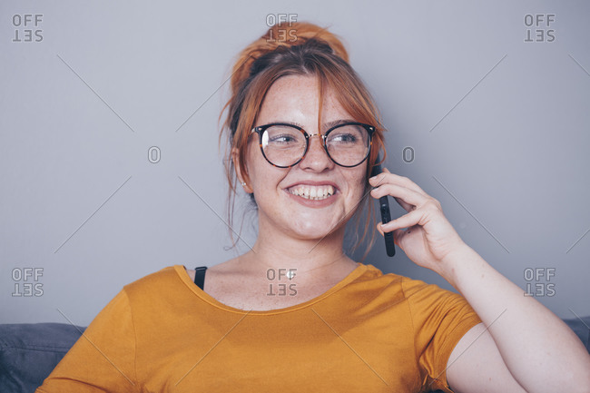 Young ginger woman sitting on sofa using cell phone